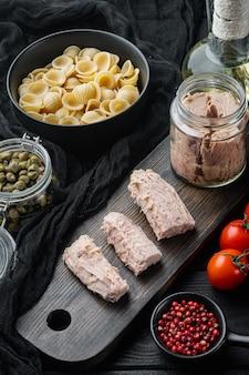 Ingredienti della pasta di tonno siciliano sulla tavola di legno nera