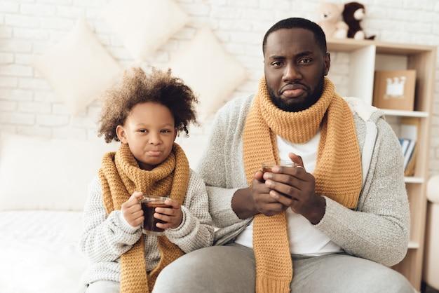 Padre e figlia malati dell'afroamericano che bevono tè.