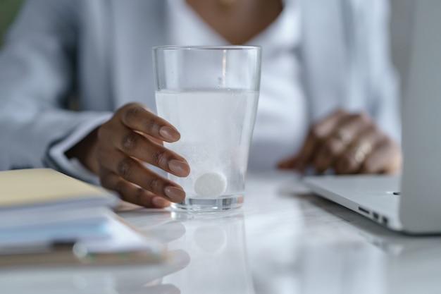 Donna di affari afro malata che tiene il bicchiere di acqua frizzante con la dissoluzione della pillola di aspirina effervescente
