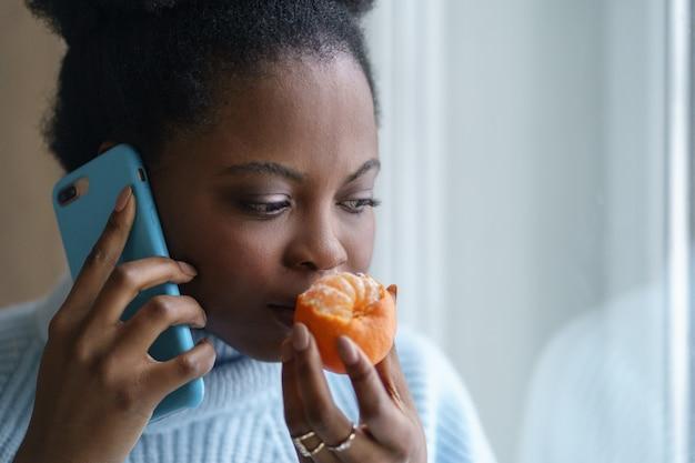 Donna afro malata che cerca di sentire l'odore di mezza arancia fresca di mandarino parlando al telefono. covid-19
