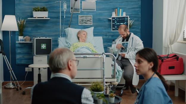 Paziente anziano malato che guarda il tablet con i raggi x dell'osteopatia