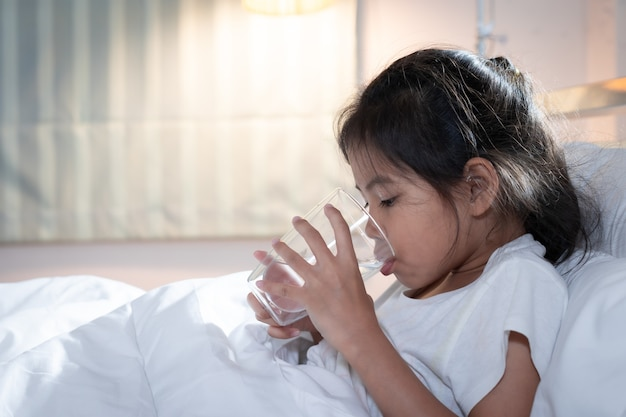 La ragazza asiatica malata del bambino sta bevendo l'acqua da un bicchiere dopo aver mangiato la medicina in camera da letto.