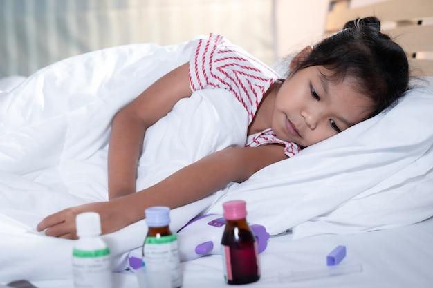La ragazza asiatica ammalata è sdraiata sul letto e guarda tristemente la medicina.