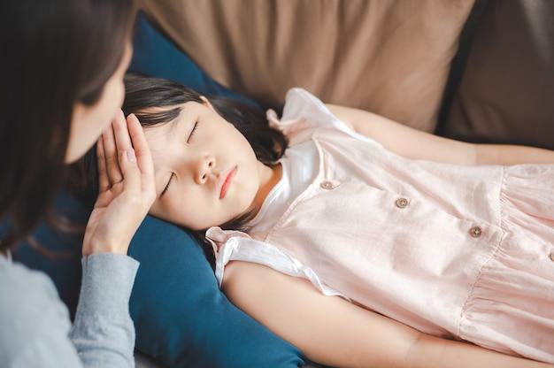Figlia asiatica malata che dorme sul divano con la febbre mentre la madre le controlla la temperatura sulla fronte