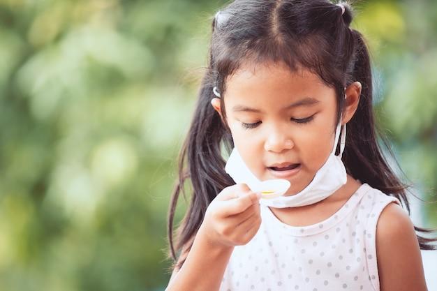 La mascherina protettiva di usura asiatica minuta della ragazza del bambino stava prendendo la medicina dello sciroppo