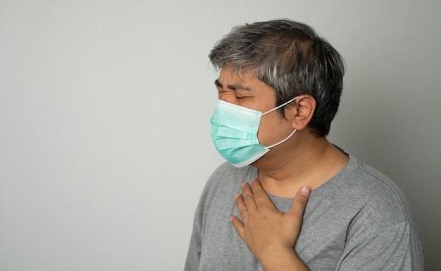 Uomo asiatico malato che indossa una maschera medica e tosse e si copre la bocca con la mano. concetto di protezione coronavirus pandemico e malattie respiratorie Foto Premium