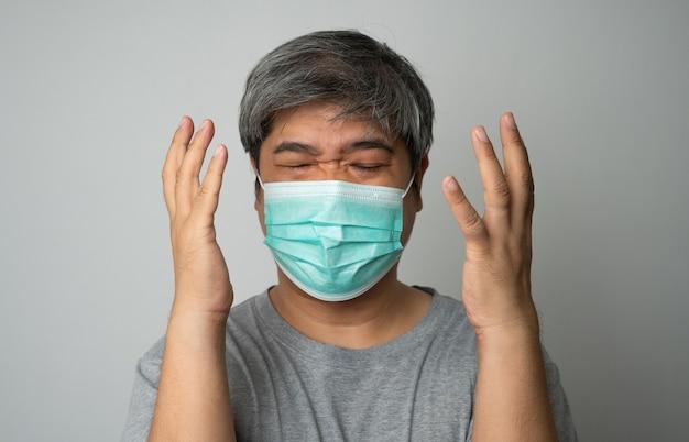Uomo asiatico malato che indossa una maschera medica e dolore alla spalla e stress. concetto di protezione coronavirus pandemico e malattie respiratorie