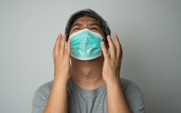 Uomo asiatico malato che indossa una maschera medica e dolore alla spalla e stress
