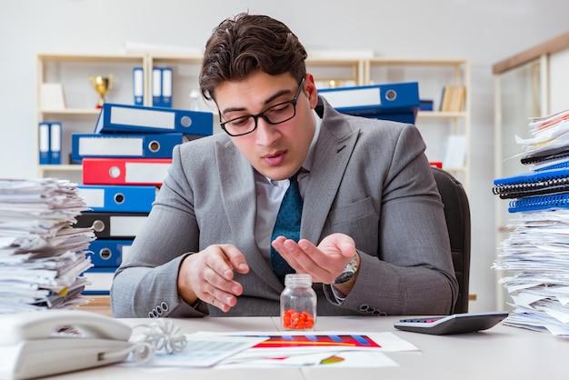 Uomo d'affari malato con le medicine allo scrittorio del lavoro