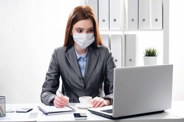 Donna di affari ammalata in una mascherina medica protettiva all'ufficio