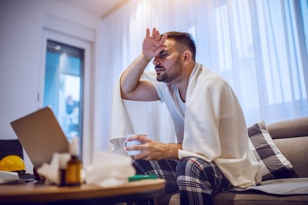 Uomo con la barba lunga caucasico malato in pigiama coperto di coperta che si siede sul sofà in salone, tenendo tazza con tè e febbre.