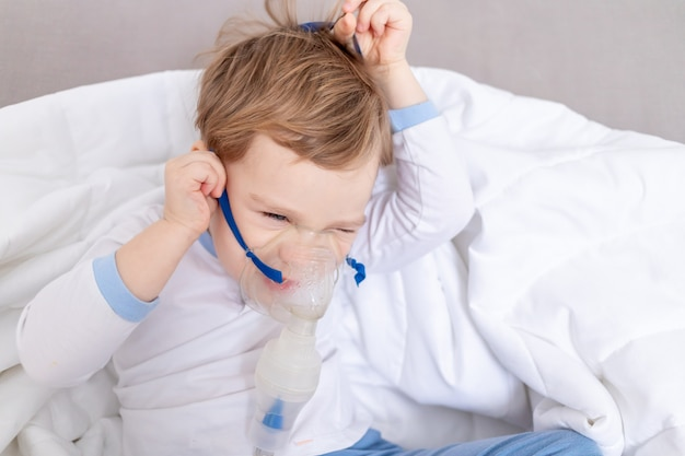 Ragazzo bambino malato si toglie l'inalatore, non vuole essere curato a casa, il concetto di salute e il trattamento inalatorio