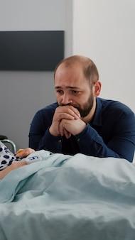 Bambina malata che indossa un tubo nasale per ossigeno e un ossimetro sul dito che monitora il battito cardiaco