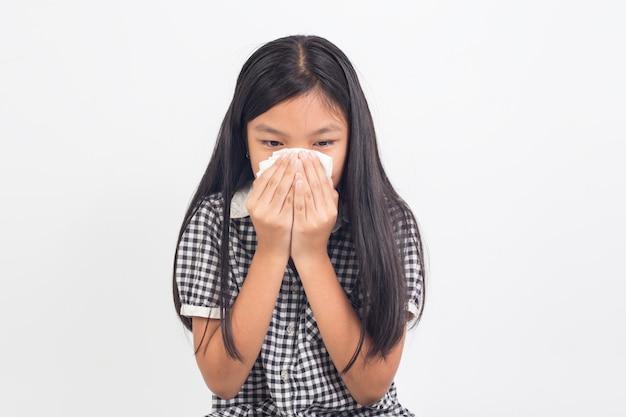 Ragazza del bambino malato che soffia il naso isolato su bianco