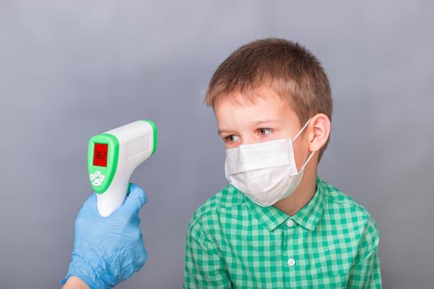 Un bambino malato viene misurato con un termometro a infrarossi