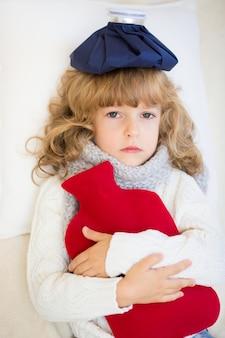 Bambino malato con febbre e borsa dell'acqua calda a casa