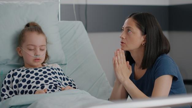 Figlia malata che dorme dopo un intervento chirurgico mentre la madre preoccupata prega per il trattamento della malattia...