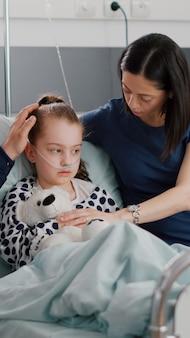 Figlia malata con tubo nasale dell'ossigeno che riposa a letto dopo aver subito un intervento chirurgico per infezione da malattia durante l'esame sanitario nel reparto ospedaliero. genitori preoccupati che spiegano il trattamento farmacologico