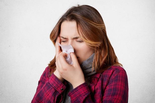 La donna disperata malata ha influenza, naso che cola, soffia il naso nel fazzoletto, ha un terribile mal di testa