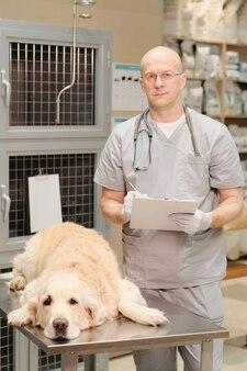 Cane malato sdraiato sul tavolo con il veterinario in piedi vicino al suo e che prende appunti nella tessera sanitaria