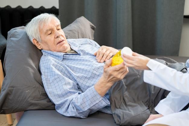 Uomo anziano malato che guarda una bottiglia di pillole tenuta da una giovane dottoressa in camice bianco che gli prescrive una nuova medicina efficace contro il covid