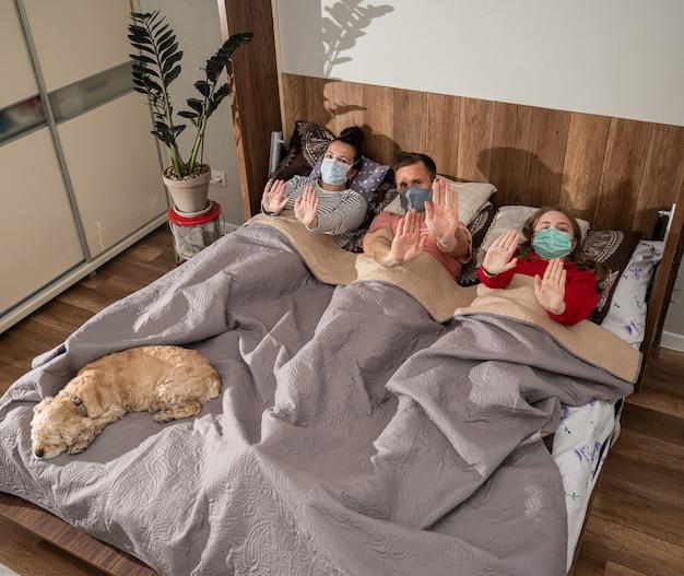 Famiglia malata in maschere protettive sdraiata a letto a casa