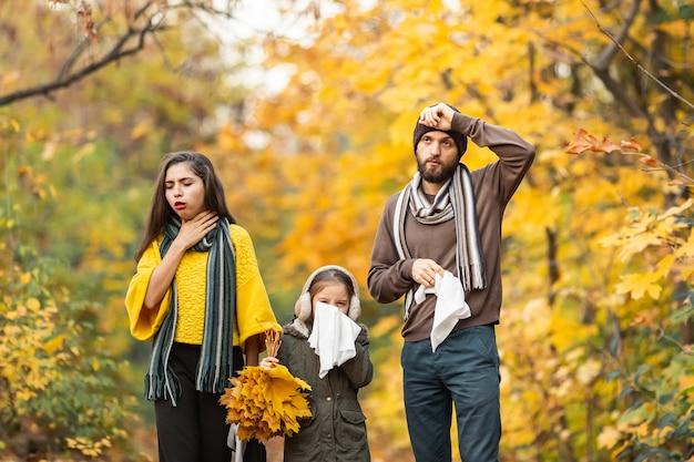 Famiglia malata in piedi in una foresta autunnale