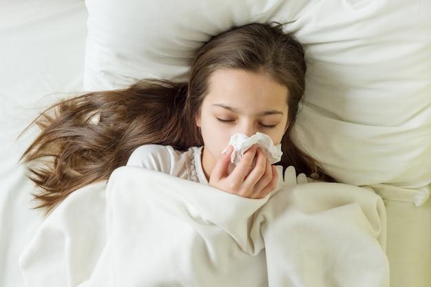 Ragazza malata sul letto che starnutisce in fazzoletto in camera da letto