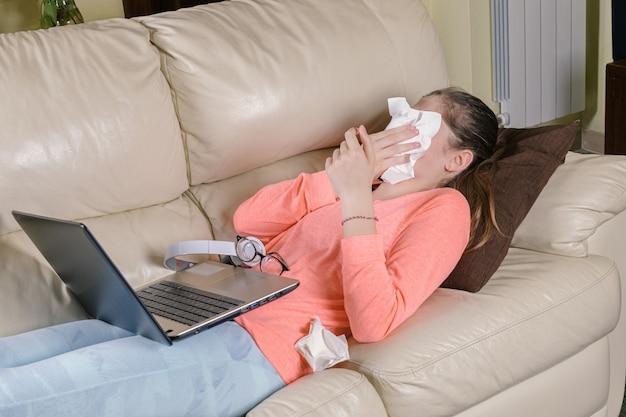 Ragazza malata che soffia il naso e lo copre con il fazzoletto con gli occhi chiusi, è sdraiato sul divano con laptop e occhiali