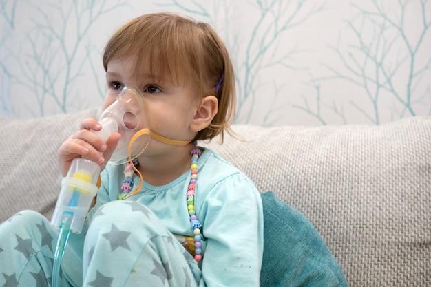 Bambina malata che tiene in mano l'inalatore e respira attraverso un nebulizzatore a casa