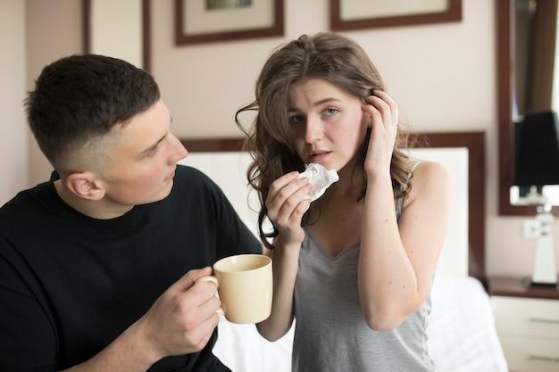Ragazza malata. ragazzo aiuta a portare il tè caldo.