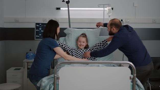 Malata paziente con tubo nasale dell'ossigeno che riposa a letto in convalescenza dopo un intervento chirurgico in corsia ospedaliera...