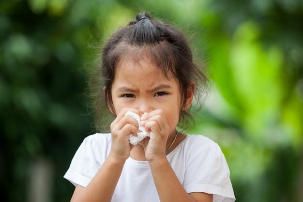 Piccola ragazza asiatica ammalata che pulisce naso