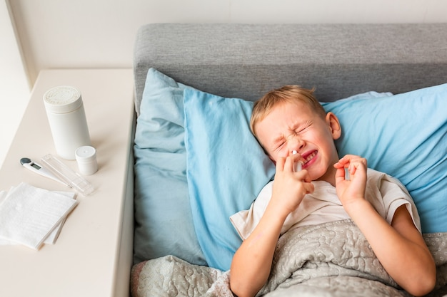 Ragazzino malato sdraiato a letto