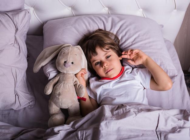 Un bambino malato in pigiama è a letto con un peluche