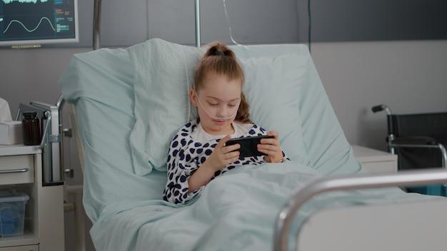 Piccolo bambino malato che riposa a letto giocando ai videogiochi online utilizzando lo smartphone che si rilassa dopo aver subito un intervento chirurgico di recupero dalla malattia. bambino che indossa un tubo nasale durante la visita medica nel reparto ospedaliero