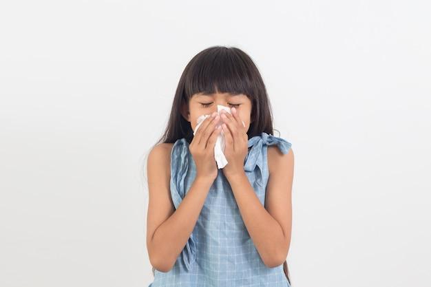 Bambina ammalata che soffia il naso isolato su bianco