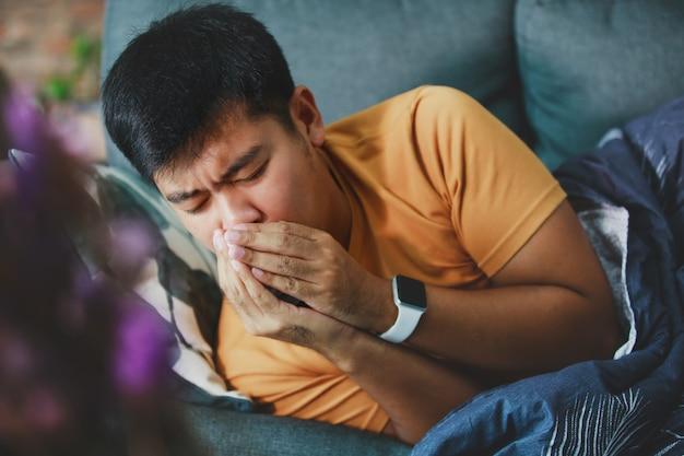 Uomo malato coperto con una tosse coperta