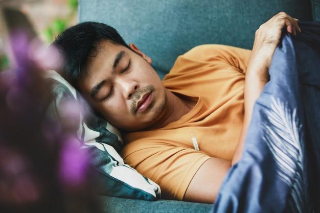 Uomo malato coperto con una coperta sdraiata sul divano