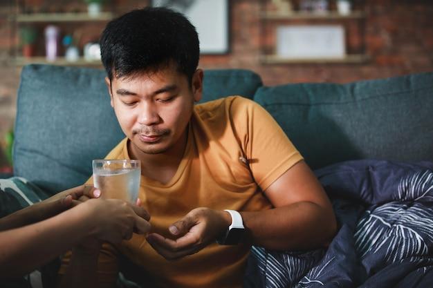 Uomo malato coperto con una coperta che prende una pillola