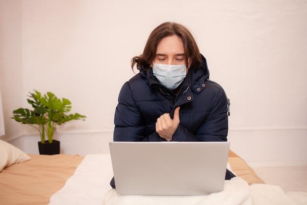 Un uomo malato si è bloccato a casa. fa molto freddo. un uomo si siede in abiti esterni dietro un laptop che indossa una maschera. quarantena domestica in inverno. coronavirus, covid.