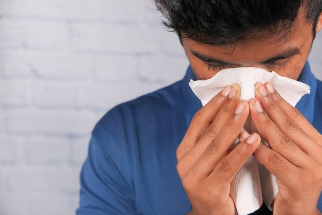 L'uomo malato ha avuto un'allergia all'influenza, starnuti e soffiando il naso