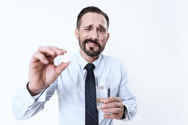 L'uomo malato tiene in mano una pillola e un bicchiere d'acqua.