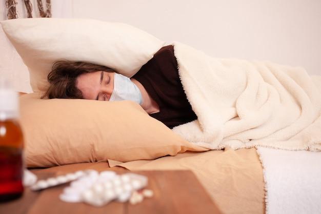 Un uomo malato in una mascherina medica sullo sfondo di compresse. quarantena domestica, coronavirus, covid. l'uomo è coperto da un cuscino e dorme, sofferente.