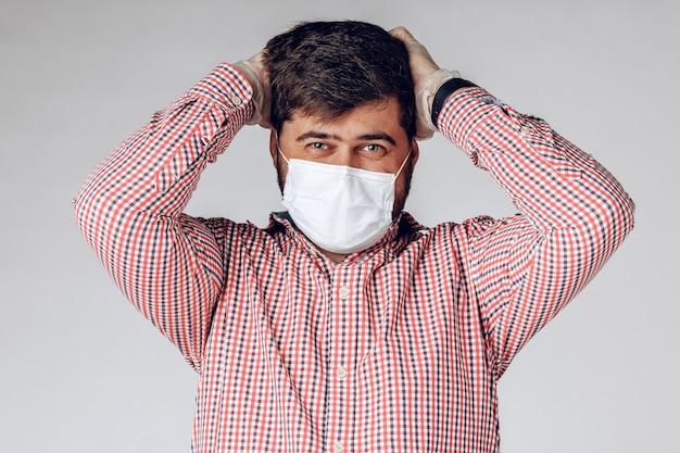 Uomo malato in maschera medica sul viso e guanti protettivi sulle mani sensazione di mal di testa.