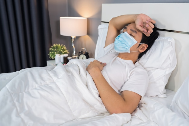 L'uomo malato nella maschera medica è mal di testa e soffre di malattie virali e febbre a letto, concetto di pandemia di coronavirus.