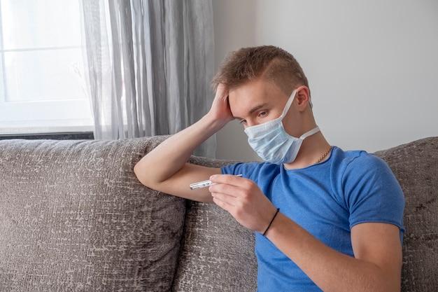 Uomo malato che si siede sul sofà e che controlla la sua temperatura con il termometro a casa.
