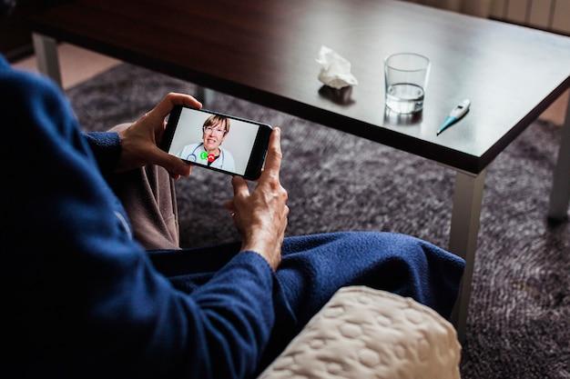 Videoconferenza uomo malato con medico utilizzando il telefono cellulare