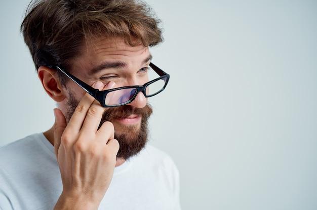 Problemi di vista dell'uomo malato in sfondo chiaro maglietta bianca