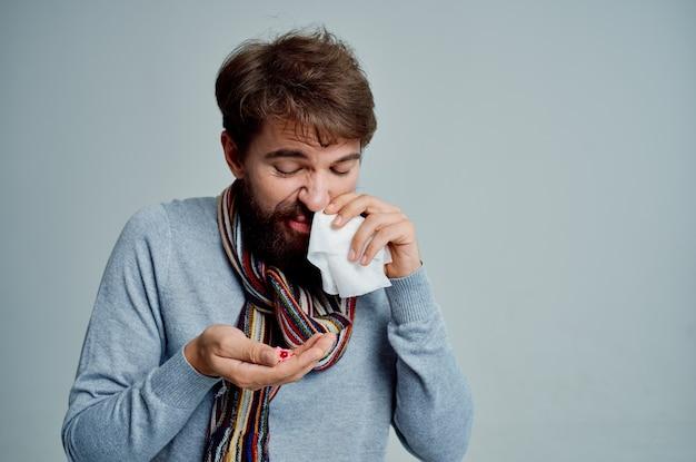Uomo malato che si pulisce il naso con un fazzoletto problemi di salute sfondo chiaro